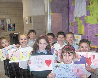 "A place for love: The entire student body at Holy Family Elementary School, 2731 Center Road, Poland, took part in a recent ""Service With a Smile"" project. Students viewed the project as an act of love and kindness. Place mats they created for residents at Maplecrest Nursing Home in Struthers are displayed by first-graders, at left from back to front, Josie Shorokey, Alaina Scavina, Grace Raymer and Julia Ranno; and in back, Joe Macejko, David Vuksanovich, Joey Carosella, Joey Morrison and Mitch Tofil. First-graders not pictured are Jack Desmond and Christina Maruca. Teacher Maria Valley presented the place mats to Lisa Daprile, nursing home representative."