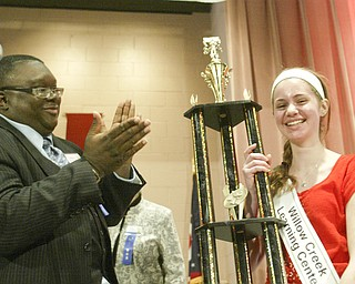 William D. Lewis The Vindicator Lauren Ritz of Willow Creek Learning Center accepts 1 rst place trouphy from spelling bee judge Rev. Lewis Macklin during Vindicator Spelling Bee Saturday.
