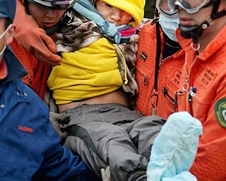 Rescue workers prepare to carry Jin Abe, 16, to a hospital in  Ishinomaki, Miyagi Prefecture, Japan, after he and his grandmother Sumi, 80, were rescued Sunday, March 20, 2011. They were rescued when Jin Abe is able to pull himself out of their flattened two-story home Sunday, nine days after the devastating earthquake and tsunami.