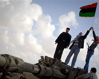 Libyan men celebrates on a destroyed tank belonging to the forces of Moammar Gadhafi in the outskirts of Benghazi, eastern Libya, Sunday, March 20, 2011. The tanks were destroyed earlier by U.S. and allied airstrikes.