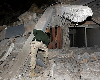 A Libyan soldier surveys the damage to an administrative building hit by a missile late Sunday, March 20, 2011 in the heart of Moammar Gadhafi's Bab Al Azizia compound in Tripoli, Libya, as he is pictured during an organized trip by the Libyan authorities. No casualties were reported.