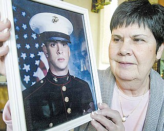 Winifred Flood holds a photograph of her son, Marine Sgt. Kenneth Flood. Winnie Flood didn't get to say goodbye to her son in person when he was deployed last month to Afghanistan because the airline she booked to North Carolina wanted an extra $300 to change the date of her flight following her son's change in deployment dates. Winifred Flood wants the airline to change its policies regarding military parents.