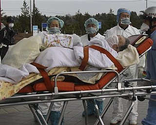 An elderly person who lives in a house about 20 miles (30 kilometers) from the Fukushima Dai-ichi nuclear plant, is transferred to receive a medical check and will be transferred to a hospital later,  in the March 11 earthquake and tsunami-destroyed city of  Minamisoma, northern Japan Tuesday, March 22, 2011.