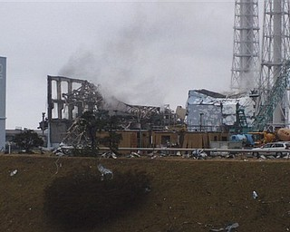 In this photo released by Tokyo Electric Power Co. (TEPCO), gray smoke rises from Unit 3 of the tsunami-stricken Fukushima Dai-ichi nuclear power plant in Okumamachi, Fukushima Prefecture, Japan, Monday, March 21, 2011. Official says the TEPCO temporarily evacuated its workers from the site. At left is Unit 2 and at right is Unit 4.