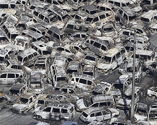 In this photo taken Friday, March 11, 2011, an aerial view shows vehicles washed away by an earthquake triggered tsunami in Hitachinaka, Ibaraki prefecture, Japan. The country's biggest recorded earthquake slammed into its eastern coast Friday.
