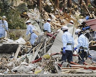 Search and rescue team members look for survivors at Minamisanrikucho, northeastern Japan, Tuesday, March 22, 2011, after the March 11 earthquake and resulting tsunami that hit the country's northeast coast.