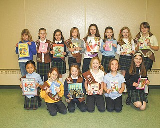 Outstanding collection: Girl Scout Troop 370 of Holy Family School, 2731 Center Road, Poland, sponsored a book drive, during which more than 500 gently used books were collected for children at the Warren G. Harding School in Youngstown. Displaying some of the books they rounded up during the drive are, in front, from left, Margaret Faur, Mya Blanco, Emily Testa, Mariah Farragher, Aubrianna McClellan and Audra Pesko, and, in back, Ally Marki, Josie Koback, Ashley Angiolelli, Kirtland Holovatick, Quinn Barton, Braiden Forsyth, Ashley Thompson and Mary Kate Kelty. Also participating in the drive was Alyssa Masternick, who is missing from the picture.