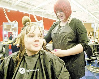 Trinity Benitez, 10, of Austintown, gets a new 'do from Aveda Institute cosmetologist Kelly VanKirk. Thirty girls in grades four through six from the Austintown Local School District were pampered Tuesday at an event organized by the Angels For Kids Foundation