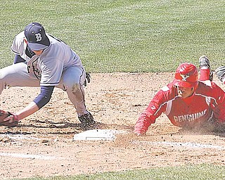 Youngstown State senior Joe Iacobucci slides back to first base to beat a pickoff  attempt.