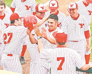 Youngstown State senior Joe Iacobucci is greeted at home plate by teammates after hitting a home run. Iacobucci and the Penguins finally get to play a home game March 22 at Eastwood Field against Penn State Behrend.