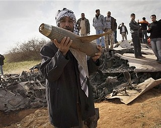 Libyans pose with the wreckage of a US  F15 fighter jet, after it crashed in an open field in the village of  Bu Mariem, east of Benghazi, eastern Libya, Tuesday, March 22, 2011, with both crew ejecting safely. The U.S. Africa Command said both crew members were safe after what was believed to be a mechanical failure of the Air Force F-15. The aircraft, based out of Royal Air Force Lakenheath, England, was flying out of Italy's Aviano Air Base in support of Operation Odyssey Dawn.