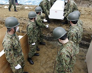 Japan Ground Self Defense Force prepare to lay a coffin during a burial ceremony for the March 11 tsunami victims in Higashimatsushima City, Miyagi Prefecture, Japan, Wednesday, March 23, 2011.