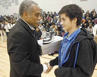 Jerome Harrell, left, principal of Wilson Middle School, Youngstown, presents a pair of shoes to eighth-grader Jonathon Flores. The shoes were presented Wednesday to several students by the family members of Jamail Johnson, who was killed Feb. 6 at a shooting a home near Youngstown State University. Johnson, 25, a YSU student had served as a mentor at the school.