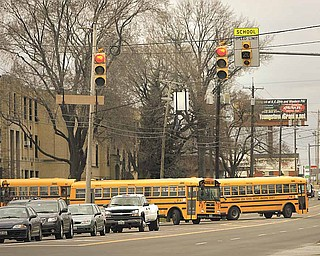 Buses leave the Boardman Center Middle School parking lot on Market Street on Tuesday afternoon into the recently installed school zone. The flashing school zone lights are being re-programmed to account for daylight-saving time.