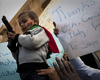 A gun was handed over to a Libyan boy during a rally in support  of the allied air campaigns against the troops of Moammar Gadhafi in Benghazi, eastern Libya, Wednesday, March 23, 2011.
