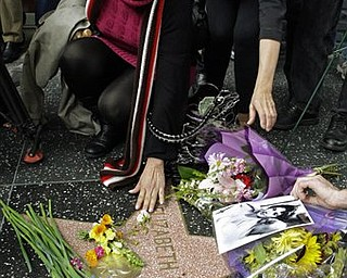A woman reaches down to touch Elizabeth Taylor's star on the Hollywood Walk of Fame in Los Angeles Wednesday, March 23, 2011. Taylor died early Wednesday of congestive heart failure at the age of 79.