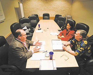 Financial planner Patrick Dougherty, left, works with Luchia and William Kingsley, right, in his Plano, Texas office, February 22, 2011. (Ron Baselice/Dallas Morning News/MCT)