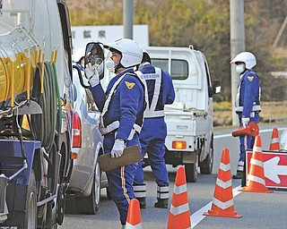 Police officers advise drivers to take a diversion at a checkpoint in Iwaki City in Fukushima Prefecture, at the 30 kilomters (20 miles) point from the tsunami-crippled Fukushima Dai-ichi nuclear power plant, northeastern Japan.
