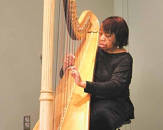 Olivia Terry, an aunt of Lorthea Hawkins, plays the harp during the reading.