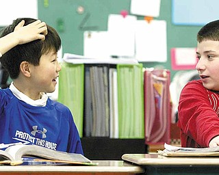 Sean Hiramatsu, 10, of Japan interacts with a classmate at McKinley Elementary School in Poland. Sean's parents sent him to the Mahoning Valley after the earthquake and tsunami in Japan earlier this month. With Sean in math class is fellow fifth- grader Mark Pompeo.