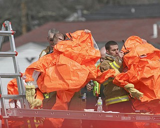 Firefighters and HAZMAT crews put on protective outfits before checking on the wrecked cars after a CSX train carrying ammonia and chlorine derailed near North Center Street in Newton Falls at about 6:45 a.m. Monday.