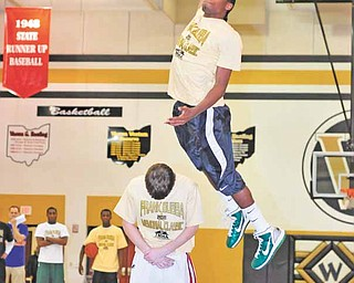 Ursuline's Khiree Gregory soars over Mooney's Danny Reese during the second round of a dunk contest at the 