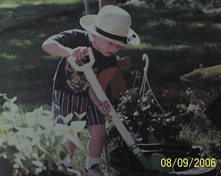 Grandma Judy snapped this shot of her grandson, Bryan, donning an authentic Amish hat while helping her plant flowers.