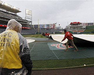 Workers cover the field as Washington Nationals practice is halted at Nationals Park on Wednesday, March 30, 2011, in Washington. The Nationals home-opener is scheduled for Thursday against the Atlanta Braves.