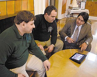 Michael Capito, right, gives a presentation on the benefits of using an iPad in business to Nick Liakaris, left, and Bill Axiotis, both of Warren and owners of The Mocha House.