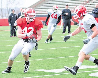 Youngstown State tight end Nate Adams (42) tries to elude strong safety Gannon Hulea (16) during the Penguins' fi rst spring scrimmage Saturday at YSU's Stambaugh Stadium.