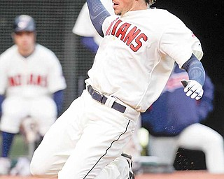 Cleveland Indians' Travis Buck slides home on a sacrifice fly by teammate Michael Brantley in the eighth inning in a baseball game against the Chicago White Sox, Sunday, April 3, 2011, in Cleveland. The Indians won 7-1.