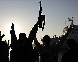 "Libyan rebels chant slogans, flash ""V"" signs and wave  guns during a welcome reception for fellow injured Libyans on board the Turkish ship Ankara, carrying 250 wounded from Misrata, as it enters the port of Benghazi, Libya Sunday, April 3, 2011. Libyan rebels want to install a parliamentary democracy in place of longtime ruler Moammar Gadhafi, one of their top leaders said Sunday, dismissing Western fears that their movement could be hijacked by Islamic extremists. (AP Photo/Nasser Nasser)"