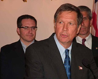 Gov. John Kasich talks to reporters before signing into law legislation requiring performance audits of certain state agencies. Public Utilities Commission Chairman Todd Snitchler is looking on in the background.