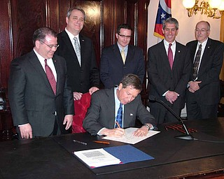 Gov. John Kasich signs into law a bill requiring performance audits of certain state agencies during
