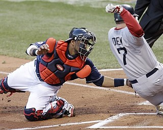 Cleveland Indians catcher Carlos Santana, left, tags out Boston Red Sox's J.D. Drew in the second inning in a baseball game Tuesday, April 5, 2011, in Cleveland. Drew tried to score on a single by Jarrod Saltalamacchia.