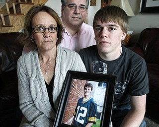 Jan, left, and Mike Rozga sit with their son Daniel on Sunday, March 27, 2011, in Indianola, Iowa, while holding a photo of their son David who killed himself last summer after dabbling with a product known as K2. Synthetic substances like K2 that mimic marijuana, cocaine and other illegal drugs are making users across the nation seriously ill, causing seizures and hallucinations so intense that thousands of them seek help at emergency rooms.
