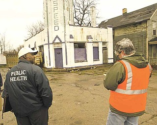 Cicero Davis, environmental health director for the Youngstown Health Department, and Brenda Williams, the city's chief building official, take note of an abandoned gasoline station at 1225 Oak Hill Ave. during a Friday inspection.