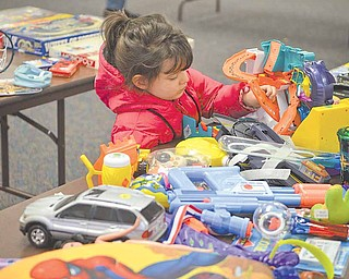 Lila Wade, 3, of Austintown inspects a table of toys at the Trash and Treasure Sale at Austintown Senior Center on Saturday afternoon. Funds raised at the event help keep the center running.