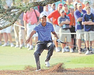Tiger Woods nearly falls backwards after hitting out of the rough on the 17th hole during the third round of the Masters golf tournament Saturday, April 9, 2011, in Augusta, Ga.