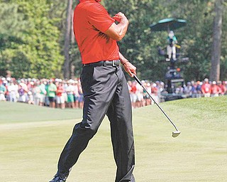 Tiger Woods reacts after an eagle putt on the eighth hole during the final round of the Masters golf tournament Sunday, April 10, 2011, in Augusta, Ga.