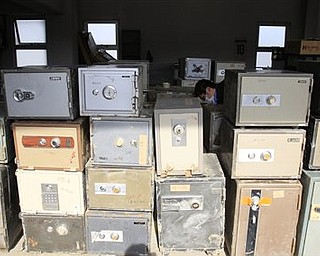 In this photo taken on April 7, 2011, a police office cleans cashboxes after they collected those from damaged houses at a police station in tsunami-hit Ofunato city, Iwate Prefecture, Japan. Safes were washing up along the tsunami-battered coast, and police were trying to find their owners, a unique problem in the country where many people, especially the elderly, still stash their cash at home.