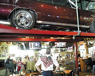 "Bowman, of Cornersburg, admires his 1967 Chevy Chevelle, on display at Quaker Steak & Lube through April. Bowman bought the car for $1,800 in 1988 and recently finished rebuilding it a second time. ""When you're out in the sun, it's really bright and brilliant,"" Bowman said of his car."