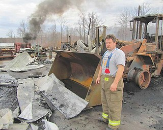 Todd Garland, Warren Township fi re chief, stands in front of one of two front loaders that were ruined at Doll Lumber, 1363 state Route 534 in Braceville Township, early Monday during a fire that destroyed a storage building and all of its contents.