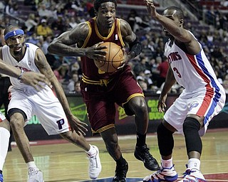Cleveland Cavaliers' Manny Harris, center, drives to the basket between Detroit Pistons' Richard Hamilton, left, and Rodney Stuckey (3) in the first half of an NBA basketball game Monday, April 11, 2011, in Auburn Hills, Mich.