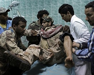 Medical staff and fellow rebels carry a Libyan rebel fighter who was injured during heavy fighting with pro-Gadhafi forces after being evacuated into the hospital of the recaptured town of Ajdabiya, Libya Monday, April 11, 2011. The Libyan rebel council rejected a cease-fire proposal presented by an African Union delegation because it did not provide for the departure of Libyan leader Moammar Gadhafi and his top associates.