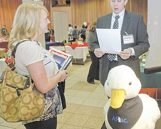 Youngstown State University student Jackie Rager of Struthers talks with Afl ac recruiter Matthew White at Tuesday's job expo at Kilcawley Center on campus. Rager was one of more than 200 students who attended the event, and many students said they felt good about their chances at landing employment.
