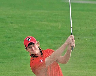 Youngstown State senior golfer and nursing major Spenser Sulzener hits his ball out of a sand trap.