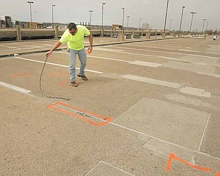 Ron Williams of SMCI Construction checks and marks the upper deck of the M2 Lincoln Avenue parking deck at Youngstown State University. The places being marked will be dug up and replaced. The deck will close Monday through Aug. 29 for repairs.