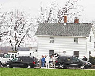 Officials remove a body from a home, Saturday, April 16, 2011, in Oak Harbor, Ohio. A sheriff's office says two adults and their three children were found dead inside their northern Ohio home and a preliminary investigation indicates murder-suicide.