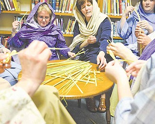 """Women of First Christian Church (Disciples of Christ), 33 N. Arlington Ave. in Niles, take a break from a recent rehearsal of the drama """"It Is Finished """" to make palm crosses. The crosses will be distributed at performances scheduled 7 p.m. today, Palm Sunday, and Maundy Thursday."""